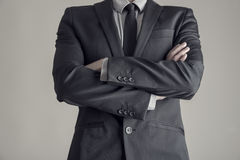 Torso of a businessman standing with folded arms. In a classic black suit, vintage effect toned image Royalty Free Stock Image