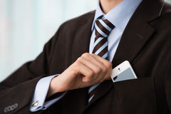 Torso of confident business man wearing elegant suit. Closeup of torso of confident business man wearing elegant suit taking mobile phone from pocket Royalty Free Stock Images