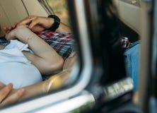torso de la gente que está mintiendo en el coche y está llevando a cabo las manos en su mano un reloj y una cadena del oro, un an imagen de archivo libre de regalías