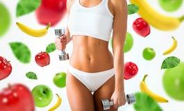 Torso de las pesas de gimnasia de elevación de una mujer joven del ajuste en blanco Imagen de archivo