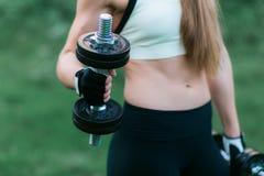 Torso de las pesas de gimnasia de elevación de una mujer joven del ajuste en fondo de la hierba verde Opinión del primer del abdo Fotos de archivo libres de regalías