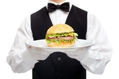 Torso del camarero con la hamburguesa en la placa Imagen de archivo libre de regalías