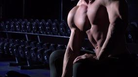 Torso des athletischen Mannes der hübschen Energie im Turnhallensitzen und im mit Dummkopf stock video