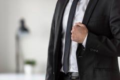 Torso di un uomo d'affari in un vestito che tiene il risvolto dei suoi stylis Fotografia Stock