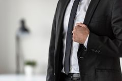 Torso eines Geschäftsmannes in einer Klage, die das Revers seiner stylis hält Stockfoto