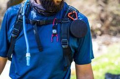 Torso of equipped hiker with speaker, compass and water pipe. Equipped hiker with speaker, compass and water pipe close up stock photography