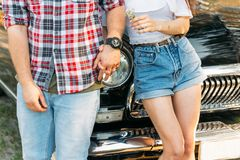 torso of a pair that is leaning on the car and holding hands in the summer. in the hands of a flower girl, on the hand of a guy we stock images