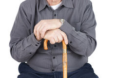 Torso of senior with cane. Great detail shot of senior man or elderly sitted and leaning on his cane, focus on hands Royalty Free Stock Photos