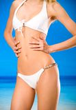 Torso of tanned woman. Torso of young tanned woman in bikini on the beach Stock Images