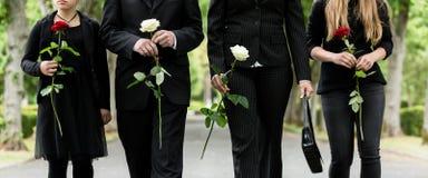 Torso van familie bij begraafplaats het rouwen stock afbeelding