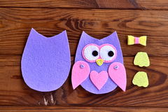 Torso, wings, legs, parts of the felt owls. Set for sewing on a brown wooden background Royalty Free Stock Image