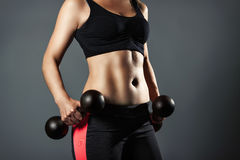 Torso of a young fit woman lifting dumbbells on dark background Royalty Free Stock Photo