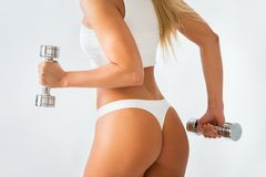 Torso of a young fit woman lifting dumbbells Stock Photos