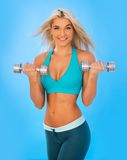 Torso of a young fit woman lifting dumbbells Stock Images