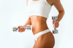 Torso of a young fit woman lifting dumbbells on white Royalty Free Stock Photos