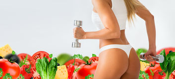 Torso of a young fit woman lifting dumbbells on white Stock Photography
