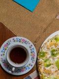 Tort robić od ciastek z kiwi plasterkami, dekorujących, kłama w białym talerzu obok spodeczka i filiżanki czarna herbata na w kra fotografia stock