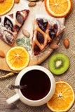 Tort z jagodami i filiżanką herbata Wysuszone pomarańcze, kiwi i migdały, obraz royalty free