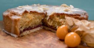Torta agria cortada del bakewell en el disco de madera verde oliva, mostrando capas de la esponja y del atasco, con la fruta del  fotos de archivo