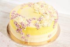 Torta amarilla con las flores poner crema Foto de archivo