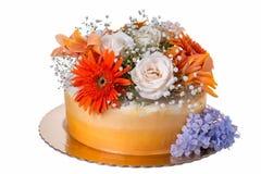 Torta anaranjada, adornada con las flores frescas Fotos de archivo libres de regalías