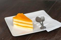 Torta anaranjada en el plato blanco Foto de archivo libre de regalías