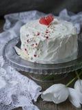 Torta blanca con el corazón rojo del chocolate en un soporte de cristal en un fondo oscuro con la tela del cordón y los tulipanes imagen de archivo