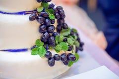 Torta blanca con las uvas y las cintas azules Fotos de archivo