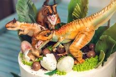 Torta blanca del día de fiesta de los niños adornada con los dinosaurios en la selva del período jurásico Postres de las ideas de foto de archivo