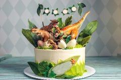 Torta blanca del día de fiesta de los niños adornada con los dinosaurios en la selva del período jurásico Postres de las ideas de foto de archivo libre de regalías