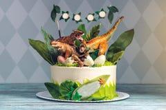 Torta blanca del día de fiesta de los niños adornada con los dinosaurios en la selva del período jurásico Postres de las ideas de fotografía de archivo libre de regalías