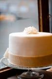 Torta blanca delante de una ventana Imágenes de archivo libres de regalías