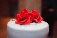 Torta blanca magnífica adornada con las flores, las rosas, las cintas y el arco rojos Foto de archivo