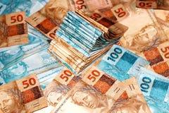 Torta brasileña del dinero con 10 y 100 notas de los reais Imagen de archivo