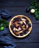 Torta casalinga con le prugne e le mele su fondo di legno scuro Immagine Stock
