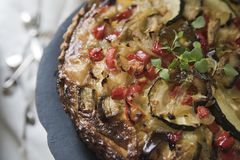 Torta caseiro com abobrinha, tomates, queijo e milho em uma bandeja, com alecrins frescos e pimenta colorida imagens de stock