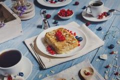 Torta, chá, café e bagas da pastelaria na madeira rústica azul Imagens de Stock Royalty Free
