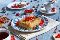 Torta, chá, café e bagas da pastelaria na madeira rústica azul Fotografia de Stock Royalty Free