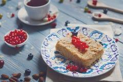 Torta, chá, café e bagas da pastelaria na madeira rústica azul Fotografia de Stock