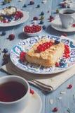 Torta, chá, café e bagas da pastelaria na madeira rústica azul Foto de Stock