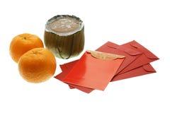 Torta china del Año Nuevo, naranjas y paquetes rojos Fotografía de archivo