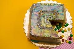 Torta coloreada del corte en un fondo amarillo, adornado Imagenes de archivo