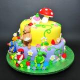 Torta colorida de la pasta de azúcar con las estatuillas de los animales Fotos de archivo