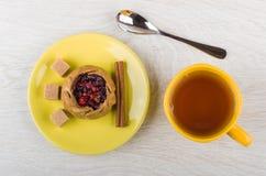 Torta com airelas, açúcar, canela nos pires, copo do chá Foto de Stock