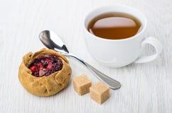 Torta com airelas, açúcar mascavado, chá no copo e colher Foto de Stock