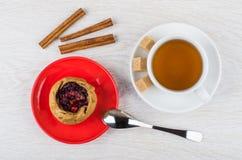 Torta com as airelas em uns pires, canela, colher, copo do chá Imagem de Stock Royalty Free