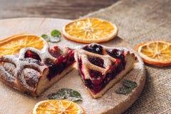 Torta com bagas em uma tabela de madeira com um guardanapo de pano decorado com laranjas secadas imagens de stock royalty free