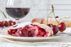 Torta com cerejas e creme de leite em um prato, toalha com uma colher o Fotografia de Stock