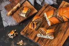 Torta com sementes de papoila em uma placa de madeira Rolo da papoila em um fundo escuro imagens de stock royalty free