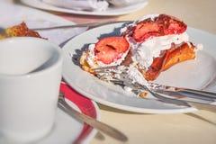 Torta comida mitad en una placa con las migas en café fotografía de archivo libre de regalías